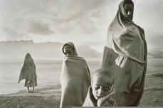 Sebastiao Salgado; Ethiopia: Refugees protected by their covers against the cold morning wind; 1984