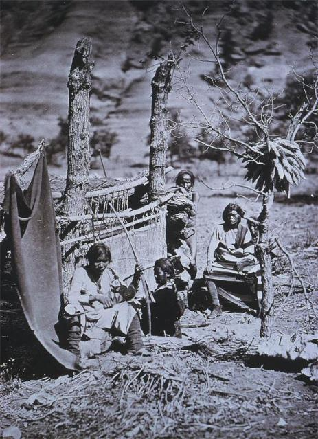 O'Sullivan, Timothy H., Navajo Family Group in Canyon de Chelle, New Mexico Territory Date 1873 Location Chelly, Canyon de (Ariz.) Material albumen silver print Measurements 27.6 x 20.2cm, A woman is weaving at a loom and one of the men is holding a bow and arrow Near Old Fort Defiance, Chelly, Canyon de (Ariz.)